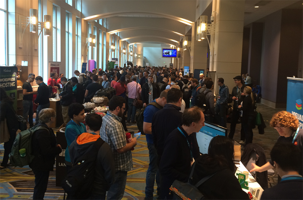 Photo of WordCamp US showing the large crowd in the sponsors area during a break.